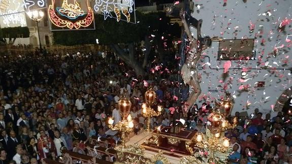 Vecinos lanzaban pétalos al trono desde sus balcones, a su paso por las viviendas. / MARÍA TORRES